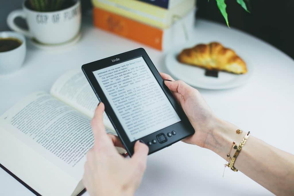 Imagem de um Kindle acima de um livro.