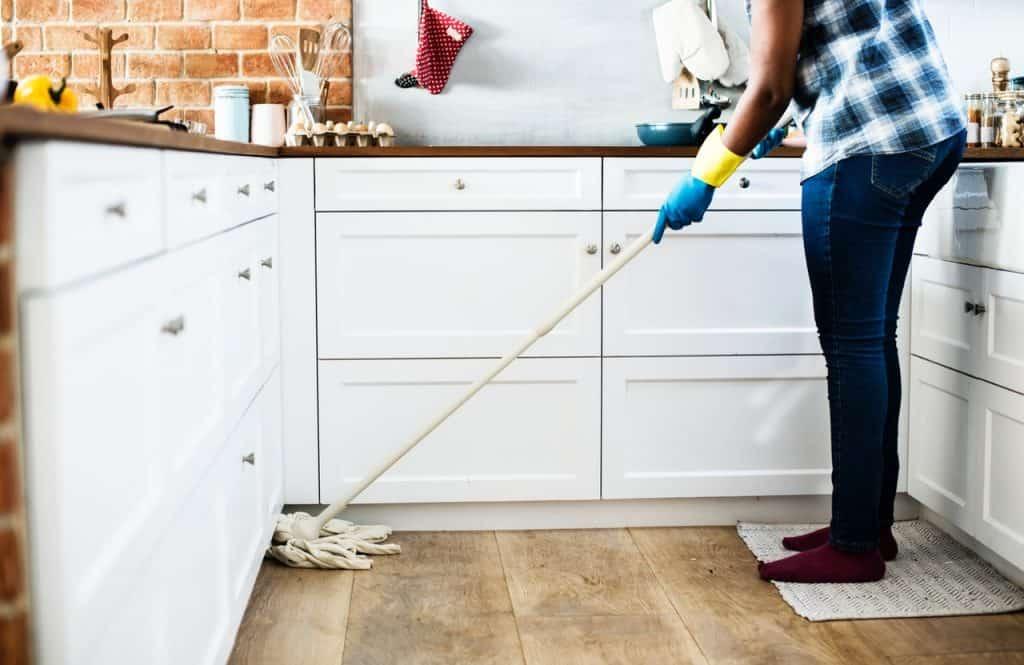 Imagem de pessoa pisando sobre tapete de cozinha branco enquanto passa pano no chão