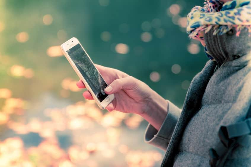 Imagem mostra uma mulher usando um smartphone da Samsung.