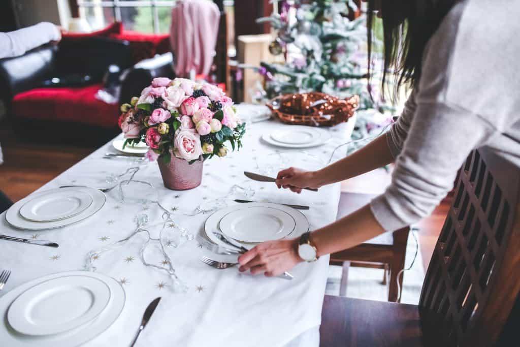 Foto de uma mulher montando uma mesa para uma refeição, com um vaso de flores rosas no centro. A tolha e os pratos são brancos.