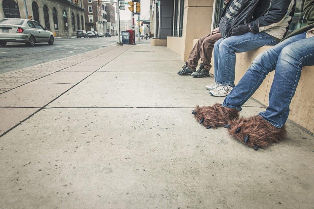 Imagem de pessoas sentadas na calça com uma delas vestindo pantufas marrons em formato de pata de animal com garras.
