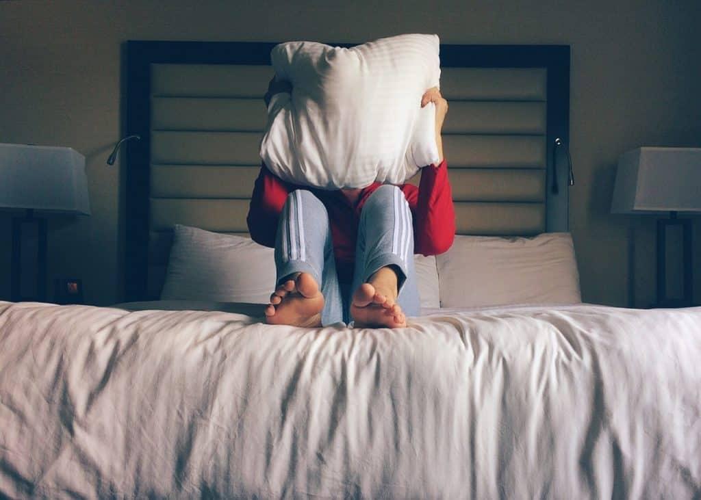 Foto mostra moça sobre a cama com travesseiro cobrindo o rosto.