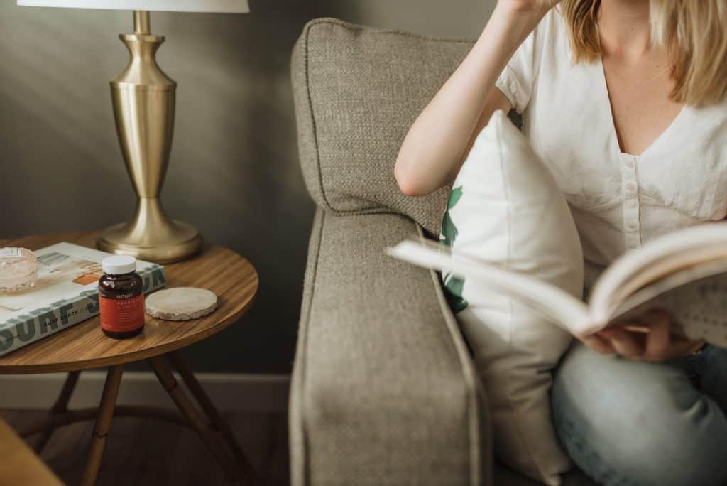 Imagem de uma mulher sentada ao lado de uma mesa de centro com um frasco de vitamina E.