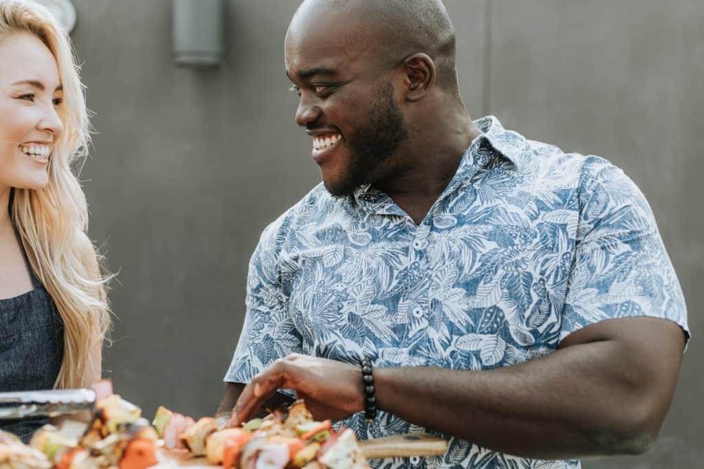 Na foto há um homem e uma mulher se olhando e sorrindo com alguns espetinhos de comida na frente.