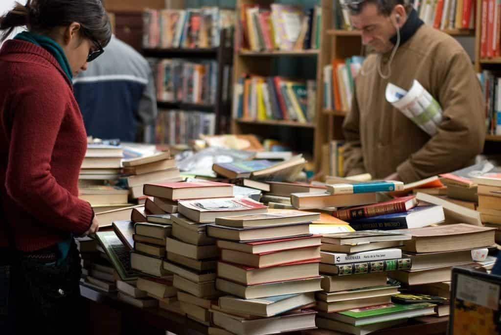 Livraria com diversas estantes e livros em cima de uma mesa. Duas pessoas observam as pilhas de livros.