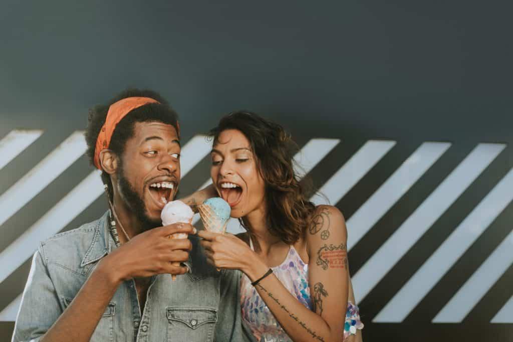 Casal brinca com bocas abertas e casquinha de sorvete nas mãos.