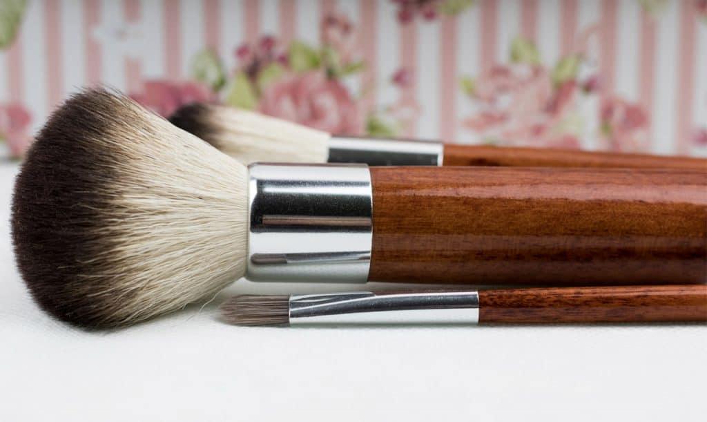 Foto de três pincéis de maquiagem, sendo um grande, um médio e um pequeno, colocados um ao lado do outro, em uma superfície branca, com um papel de parede estampado ao fundo.