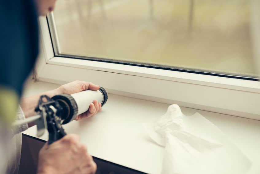 Pessoa aplicando silicone em janela.