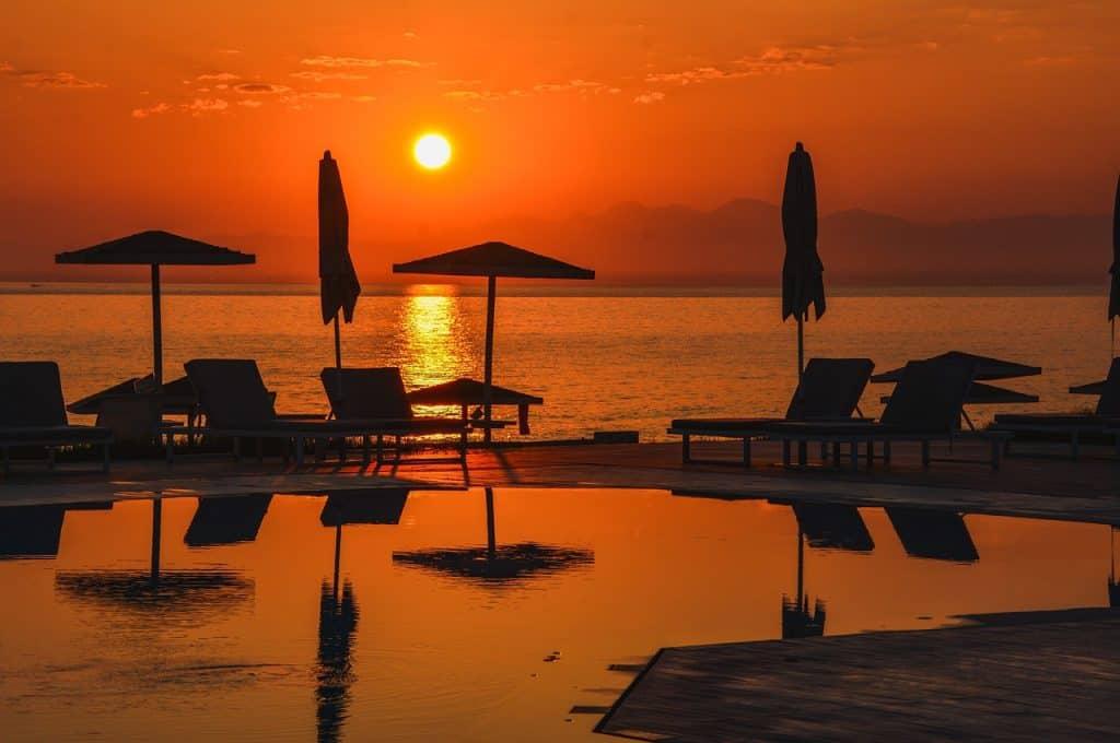 Imagem de piscina em frente ao mar com o sol se pondo.