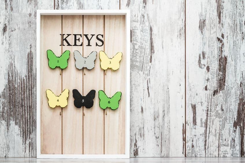 Um porta-chaves de madeira com detalhes de borboletas.