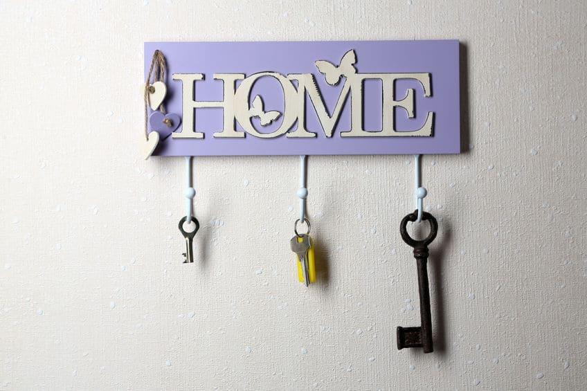 O braço de um homem pegando a chave no porta-chaves perto da porta.