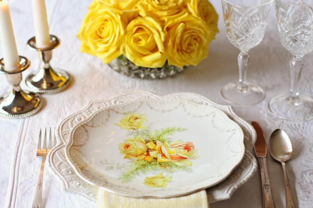 Imagem de mesa de jantar com sousplat de louça branca ornamentado sob prato com motivos florais.
