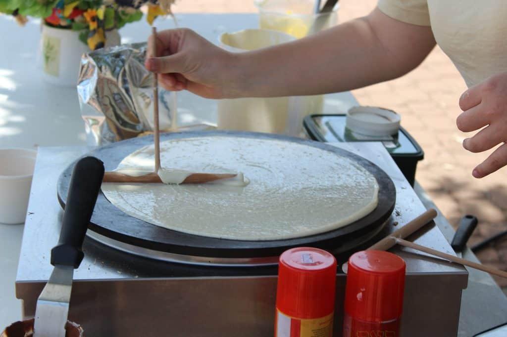 Imagem de um homem mulher preparando crepe francês.