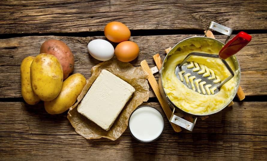 Imagem de panela com batata amassada e espremedor com outros ingredientes ao lado, sobre mesa.