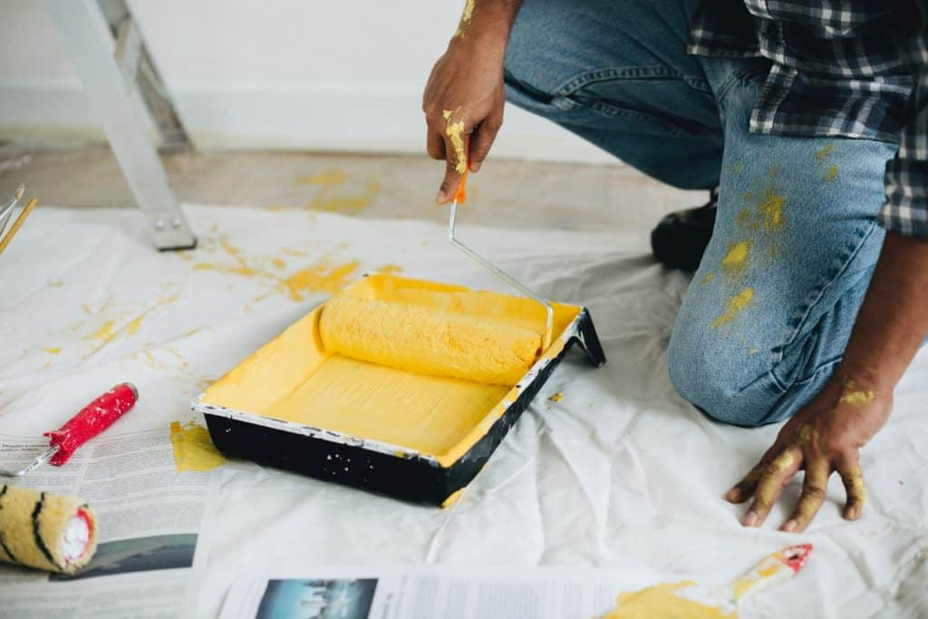 Foto de homem agachado em frente a recipiente com tinta amarela com o rolo de espuma dentro.