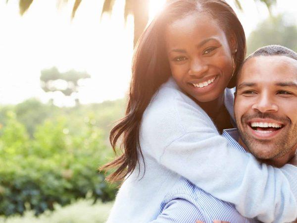 Na foto está um casal abraçado sorrindo.