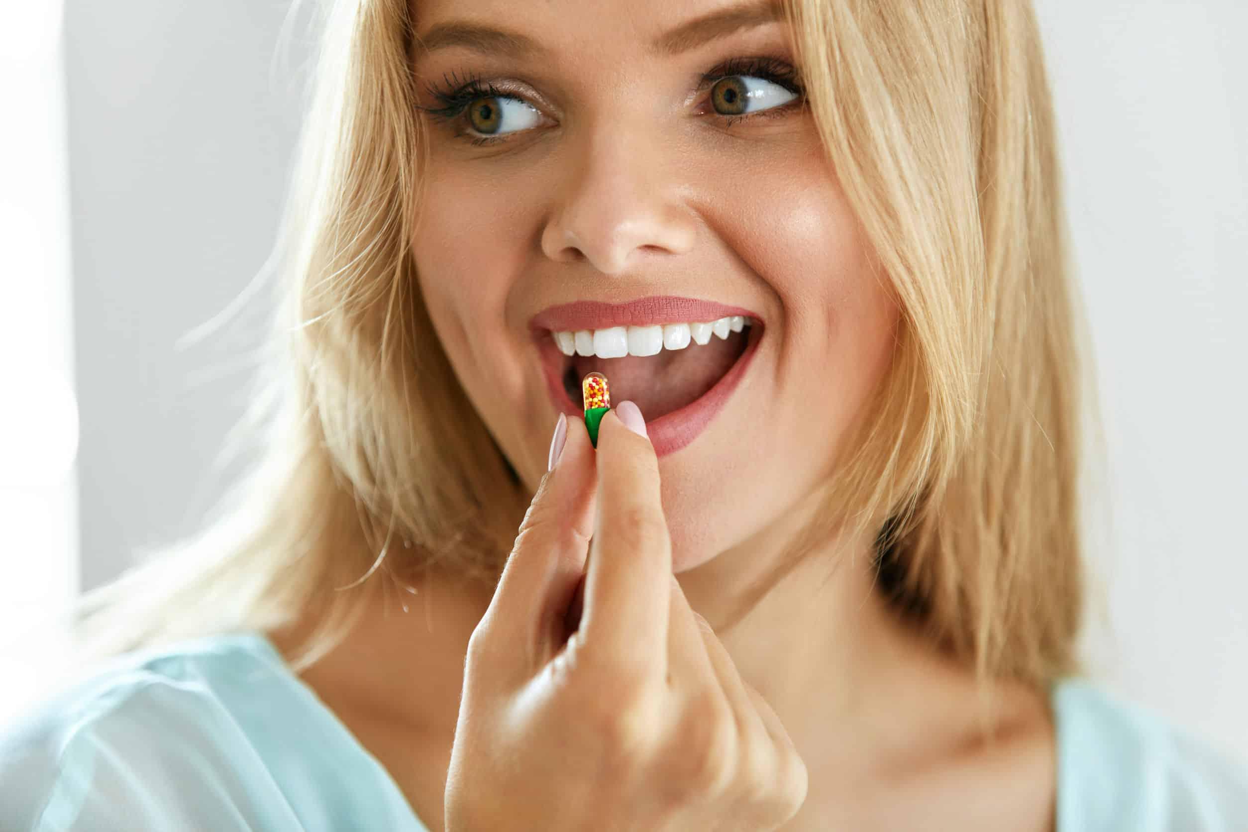 Na foto uma mulher loira segurando uma cápsula de remédio.