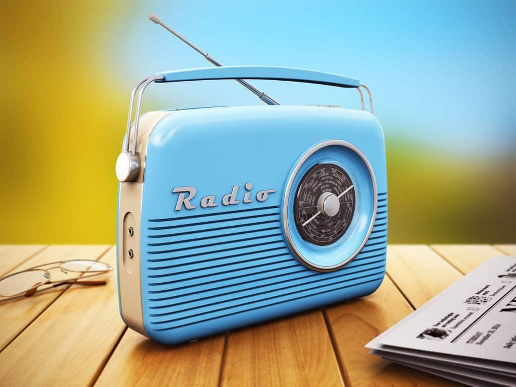Blue portable radio on wooden table next to newspaper