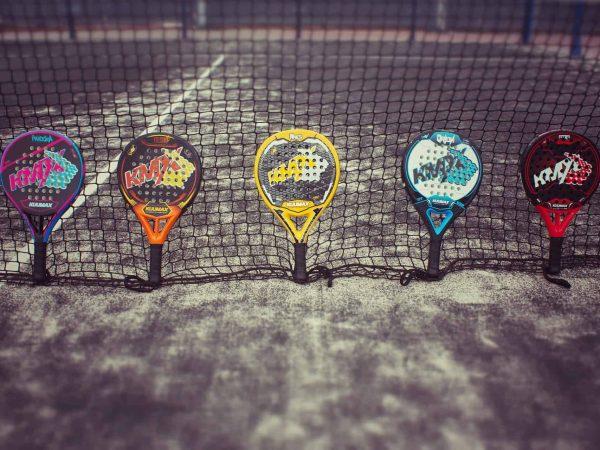 Imagem mostra cinco raquetes de padel encostadas na rede em uma quadra.