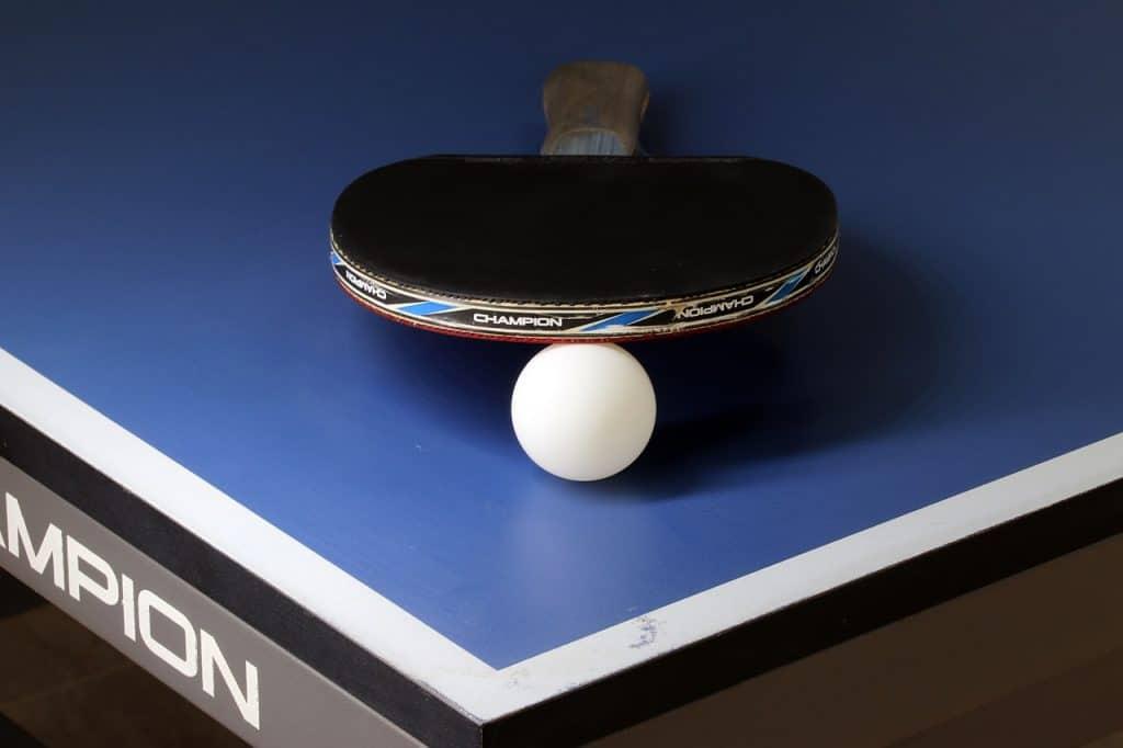 Na foto uma mesa de tênis de mesa com uma raquete e uma bolinha.