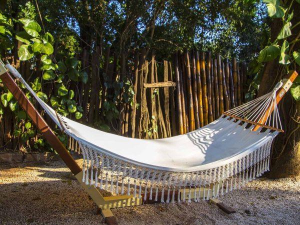 Rede de descanso branca apoiada em dois pedaços de madeira em um quintal.