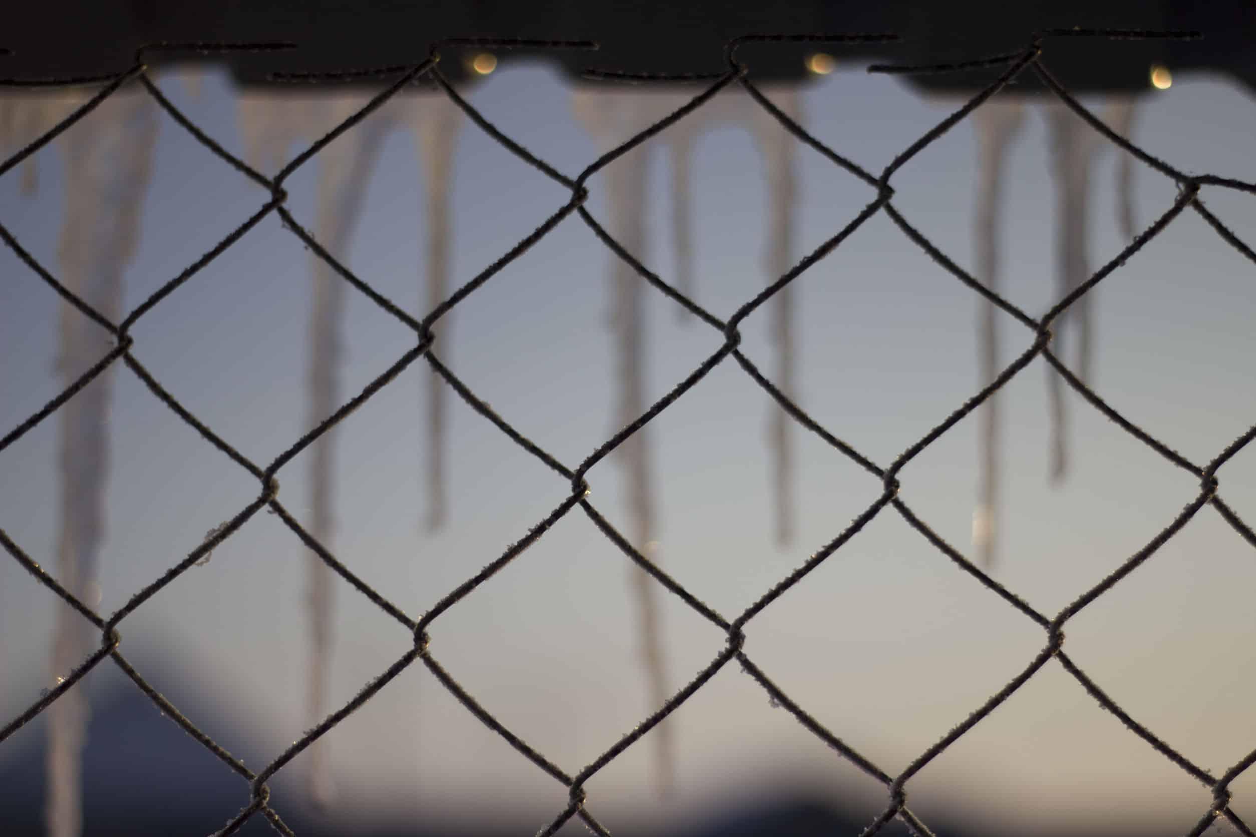 Na foto está um pedaço de uma janela com rede de proteção preta.
