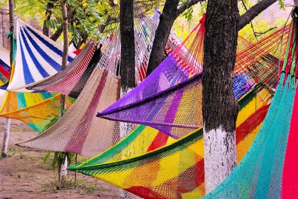 Redes de diversas cores e modelos penduradas em árvores.