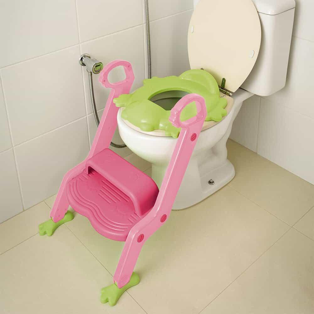 Imagem redutor de assento infantil verde com escada cor de rosa em vaso sanitário padrão.