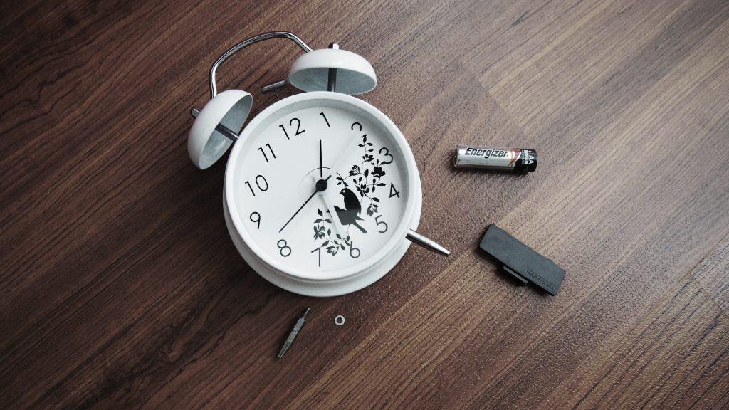 Imagem mostra um relógio-despertador, com sua tampa traseira, uma pilha comum, uma chave e uma rosca dispostas aos seu redor.
