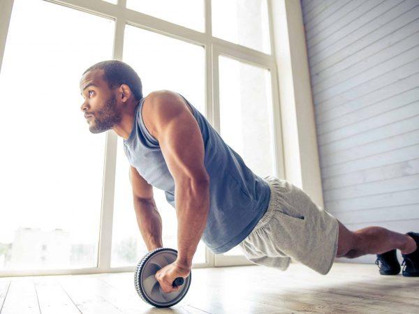 Imagem de homem se exercitando com uma roda de exercícios abdominais.