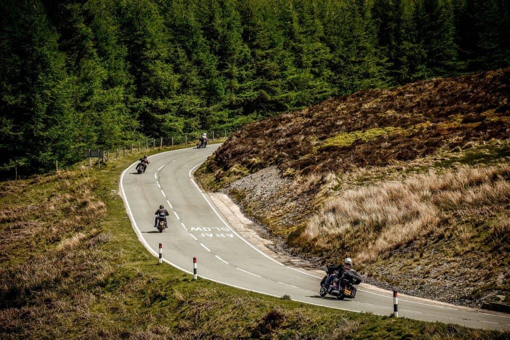 Imagem mostra um grupo de motociclistas andando em uma estrada.
