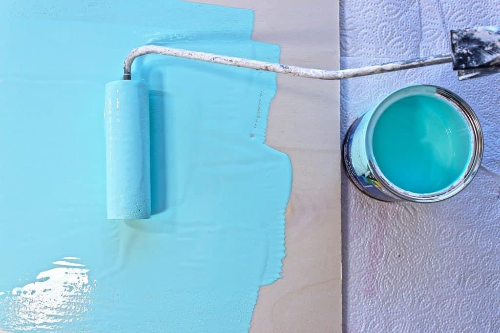Imagem de rolo de espuma com tinta azul ao lado do balde de tinta.