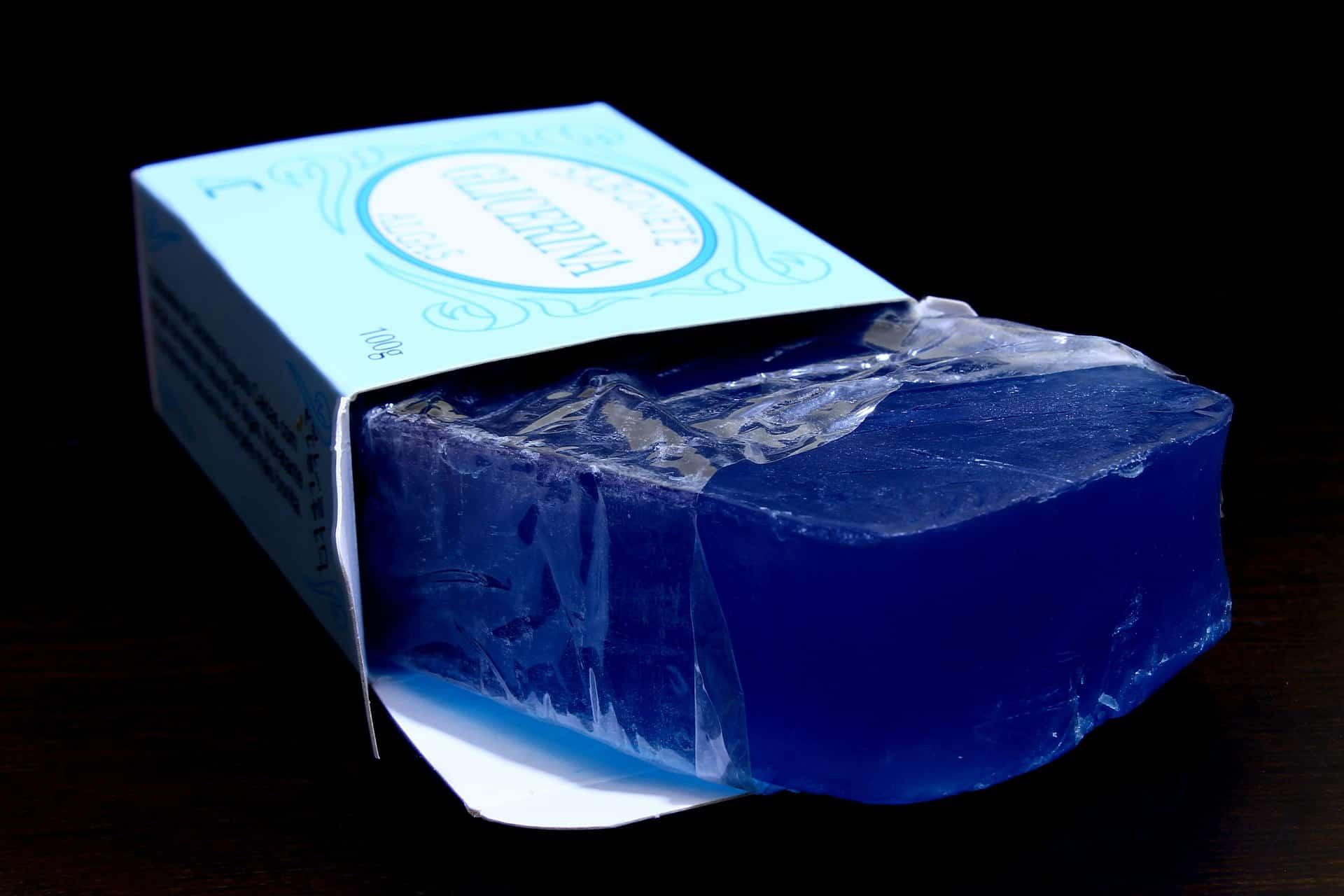 Sabonete azul glicerinado parcialmente retirado da embalagem sob fundo escuro.