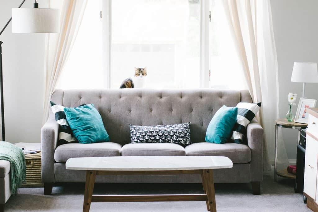 Sala de estar com mesa de centro comprida e móveis de cor clara.