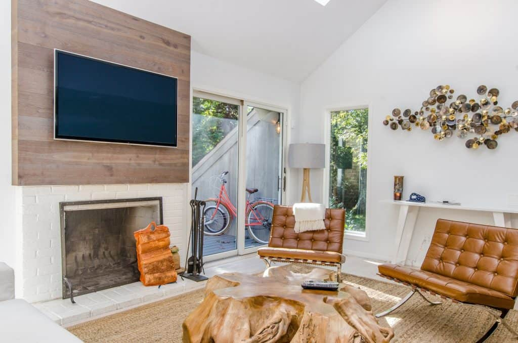 Televisão grande presa na parede de uma sala de estar.