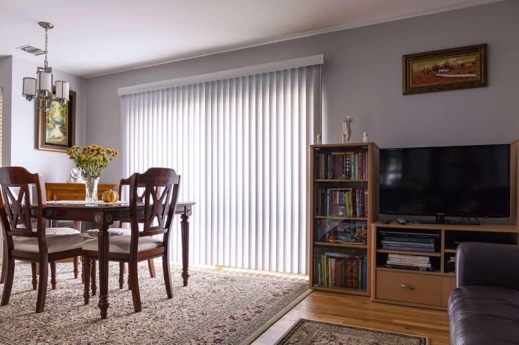 Imagem de sala de jantar com persiana na porta.