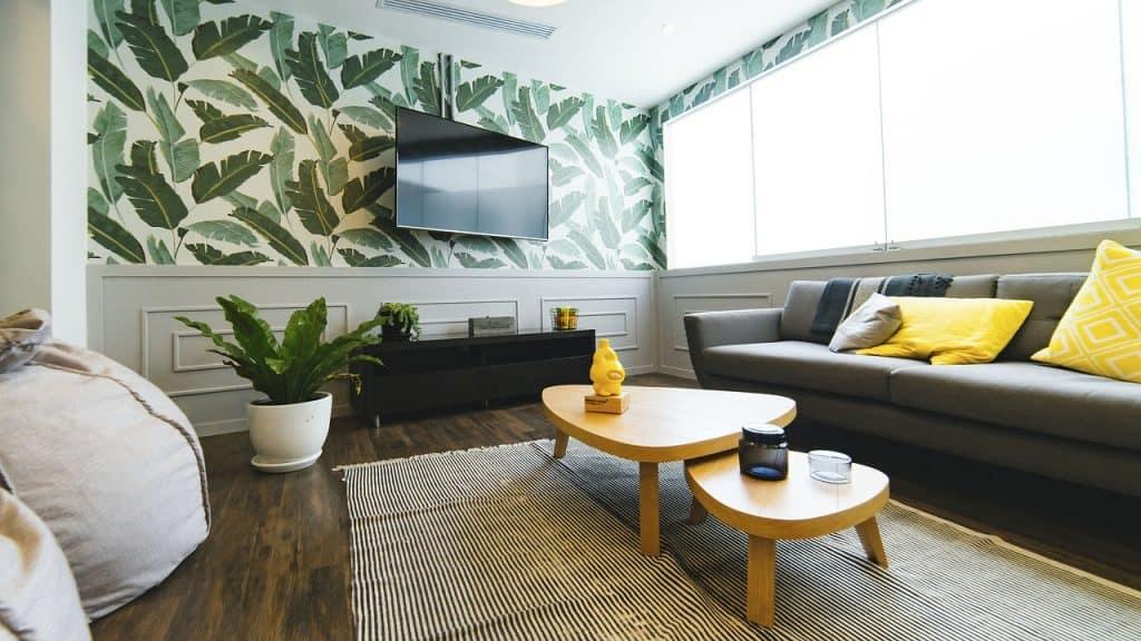 Sala de estar com sofá, pufes, mesinha de centro e televisor grande preso na parede.