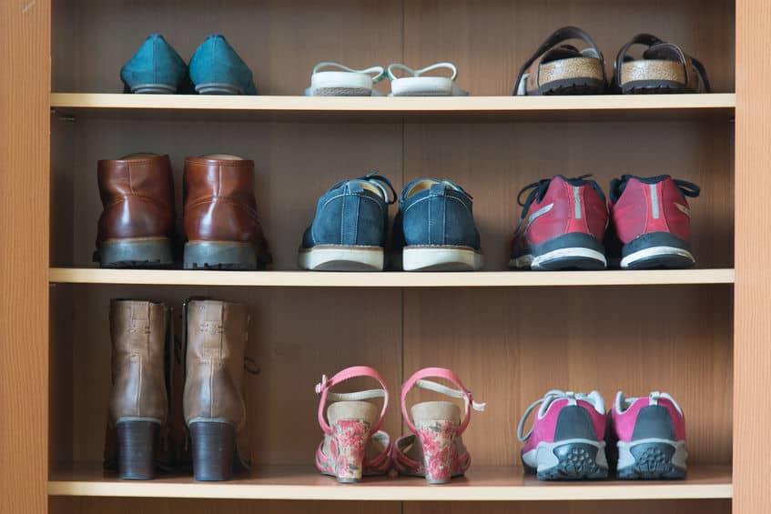 Imagem de sapateira de madeira com alguns sapatos.