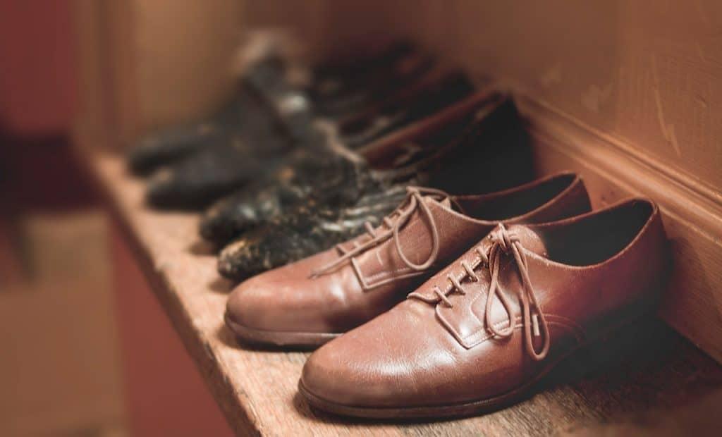 Foto de três pares de sapatos vintage apoiados em uma superfície de madeira. O par da frente está em evidência.