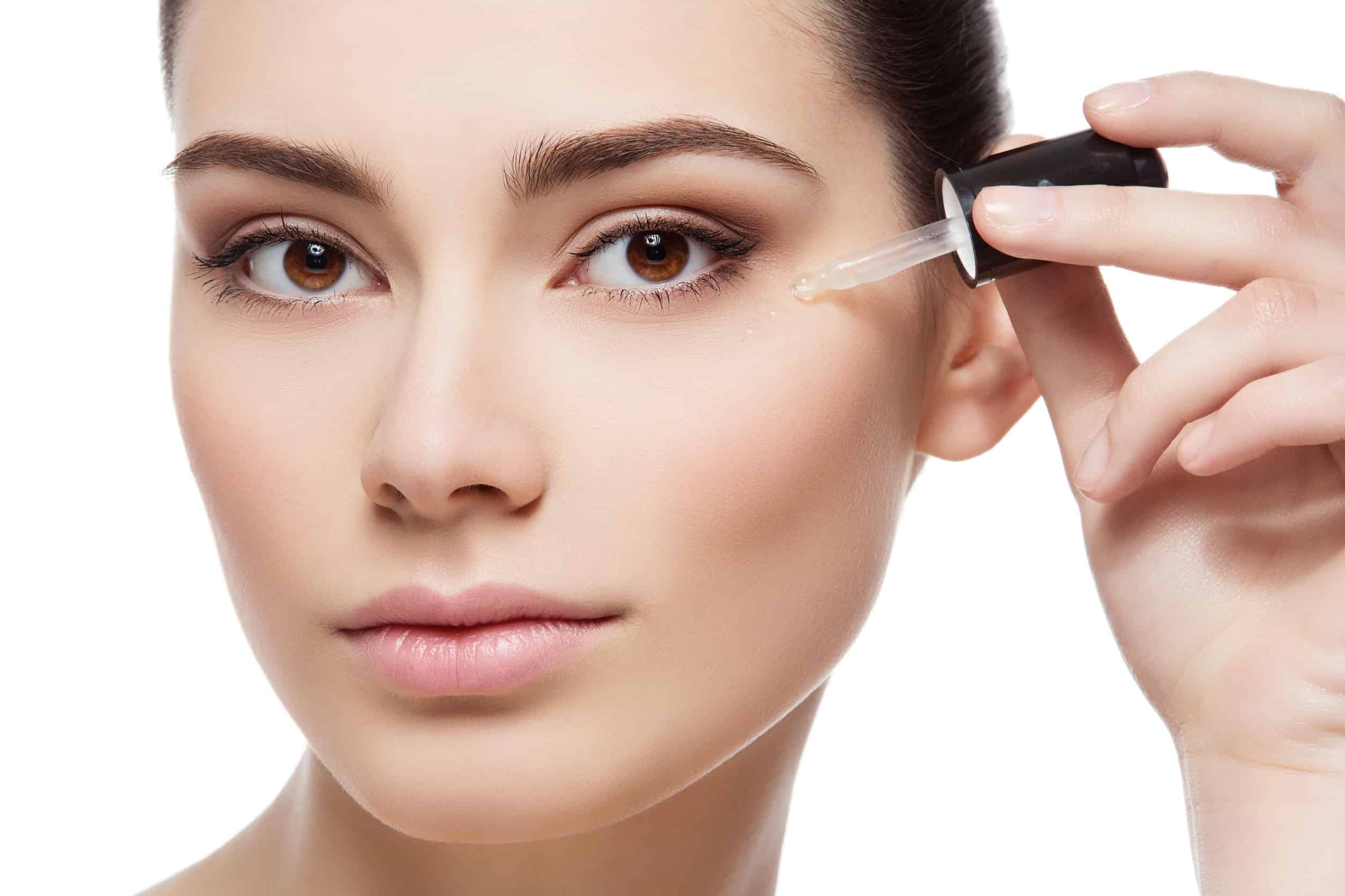 Foto do rosto de uma mulher, que está aplicando sérum facial na região acima da maçã do rosto. Ela está de cabelo preso e com a pele limpa.