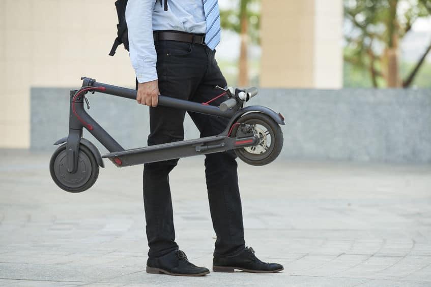 Imagem de um homem carregando seu patinete elétrico dobrado.