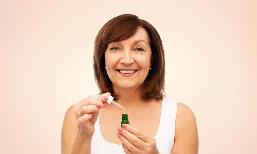 Foto de uma mulher sorrindo e segurando um sérum facial.