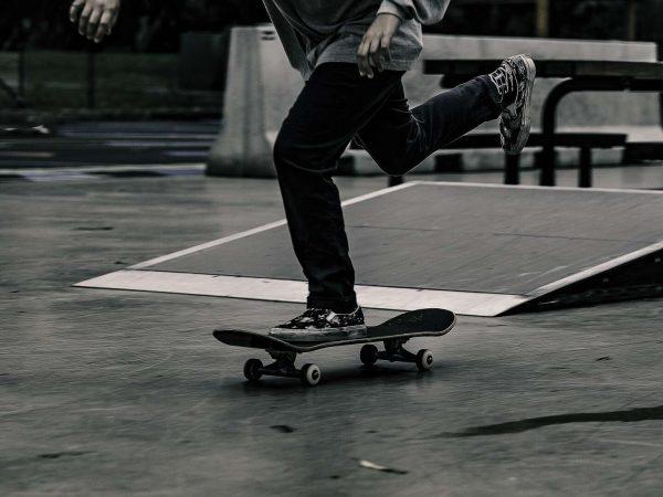 Imagem em preto e branco mostra uma pista com um skate em destaque e um skatista andando sobre ele.