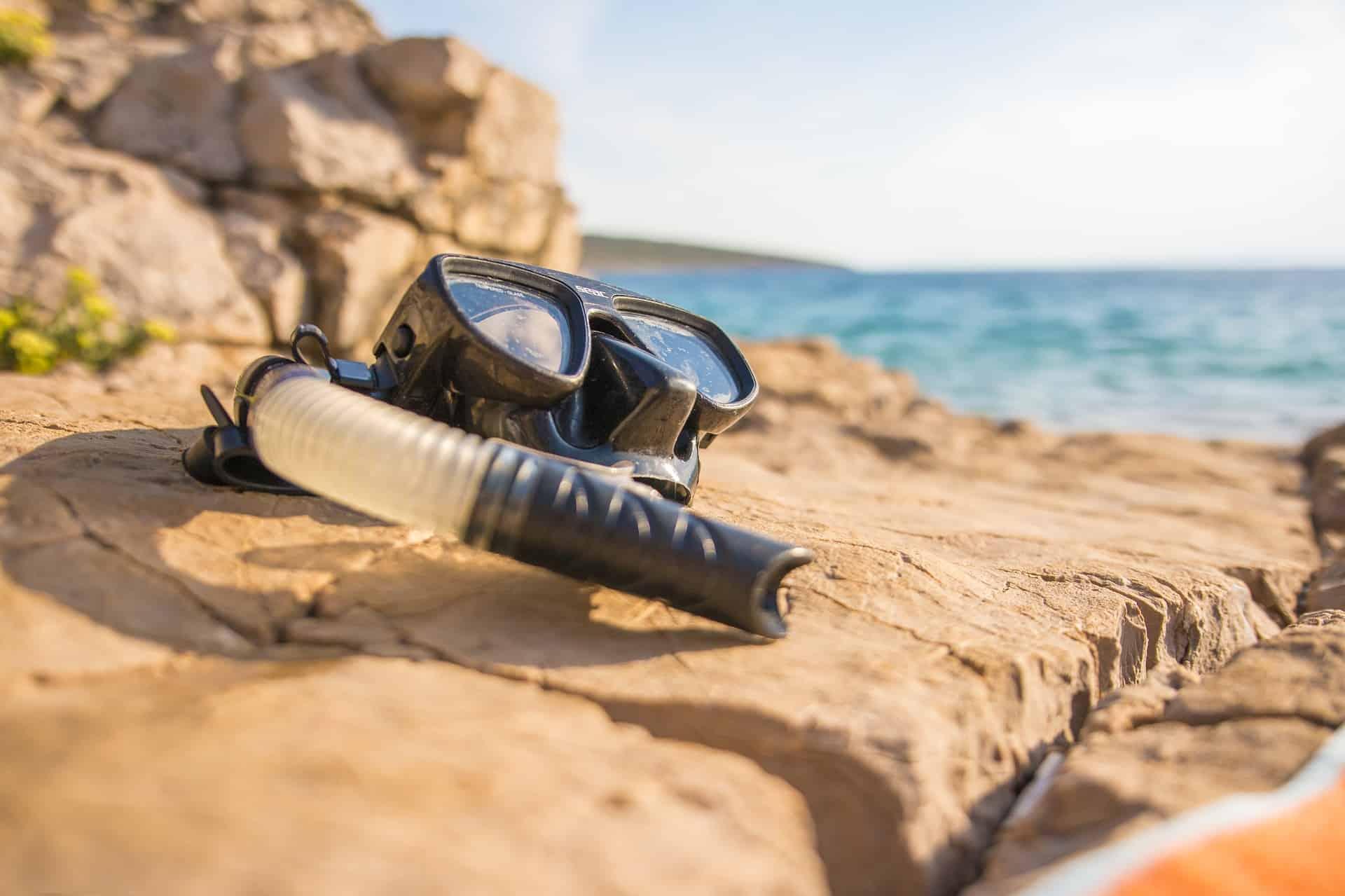 Imagem de snorkel sobre pedra em praia.