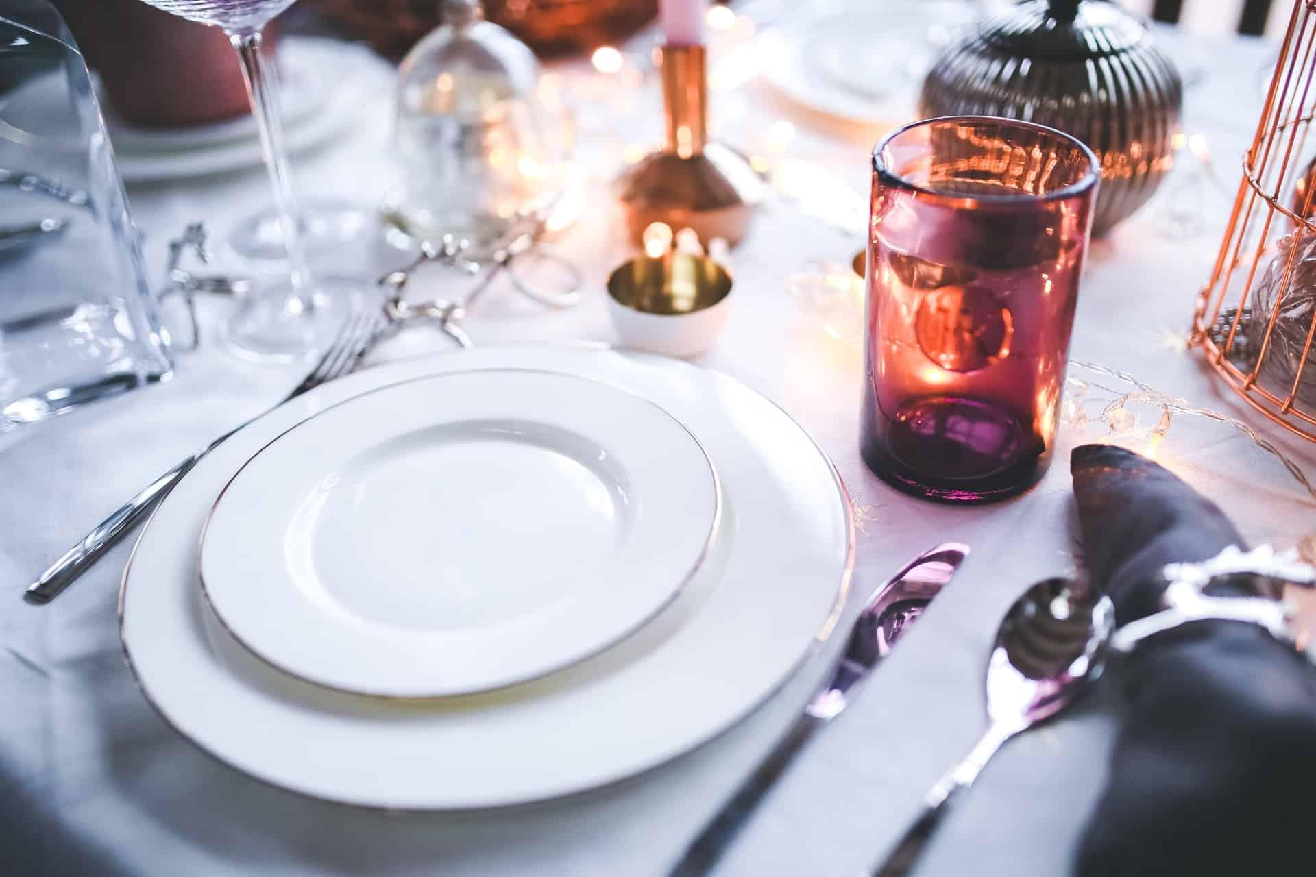 Imagem de mesa de jantar com sousplat e louça branca com bordas douradas.