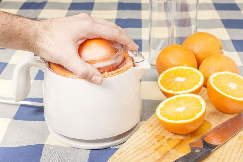 Mão espremendo laranja em um espremedor elétrico, com pedaços de laranja cortados e faca sobre tábua de madeira.