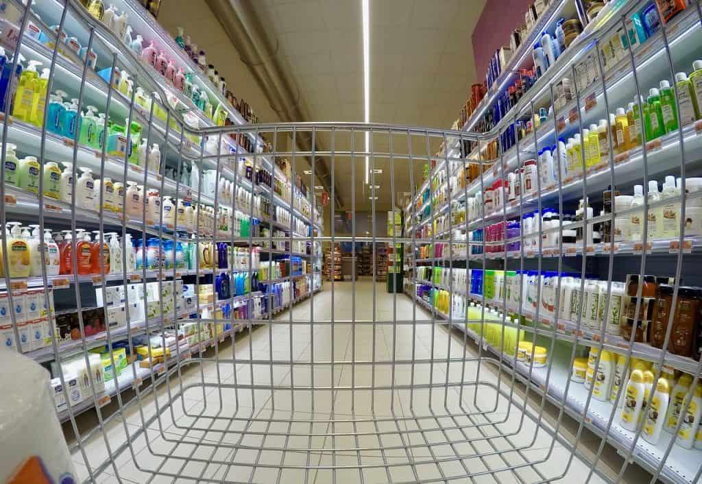 Visão de um carrinho de supermercado mostra prateleiras repletas de sabonetes líquidos e em barra.