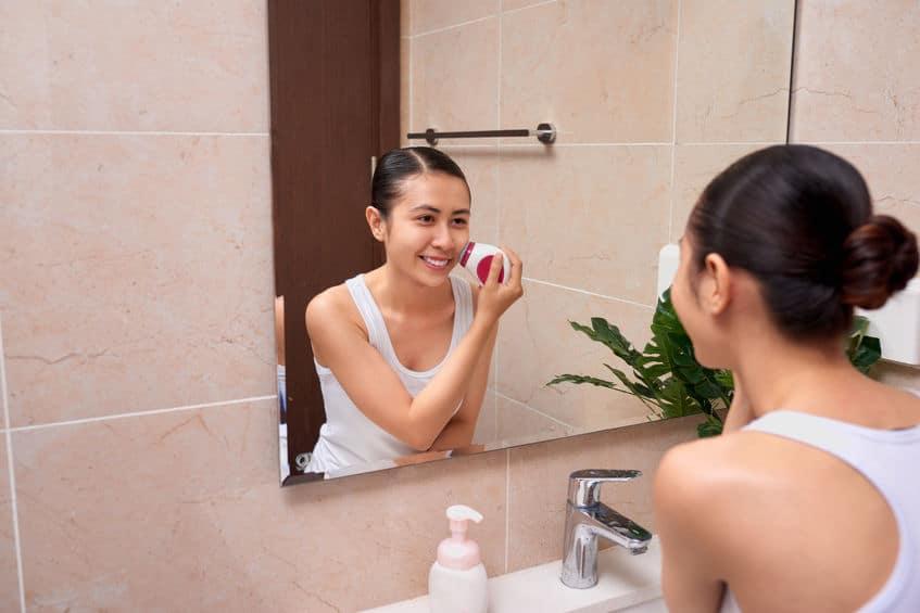 Imagem de mulher utilizando massageador facil em frente ao espelho.