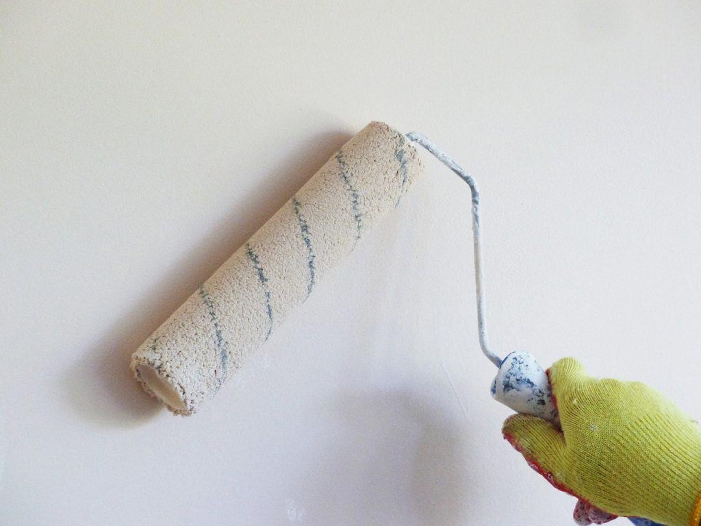 Imagem de pessoa segurando rolo de espuma grande com tinta branca.