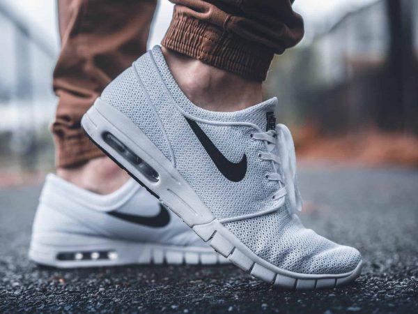 Imagem de pé masculino vestindo tênis Nike branco com amortecedor aparente.